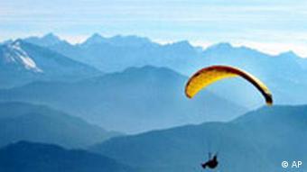 Ein Gleitschirmflieger fliegt vor der Kulisse der Alpen