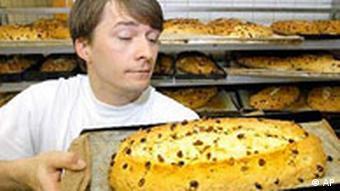 Bäckermeister Ronald Morenz in seiner Bäckerei in Dresden holt einen Stollen aus dem Backofen