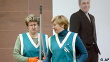 Two cleaning women talk in front of a portrait of Mikhail Khodorkovsky, head of Russia's largest oil company Yukos, in company's headquarters in Moscow, Tuesday, Oct. 28, 2003. Khodorkovsky, Russia's richest man, was jailed Saturday on charges of tax evasion, fraud and forgery. Many perceive the four-month investigation into Yukos oil and his other companies as an attack organized by some of President Vladimir Putin's associates to avenge the tycoon's political activities, including funding of opposition parties in the run-up of the Dec. 7 parliamentary elections. (AP Photo/Alexander Zemlianichenko)