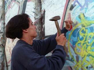 Un portugués trata de llevarse una parte del muro.