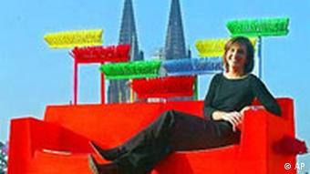 Eine Frau, die auf einem Sofa erhöht sitzt mit einigen Besen im Hintergrund