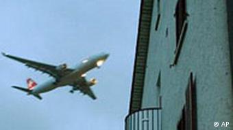 Flugzeug fliegt an einem Haus vorbei