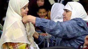 A Muslim woman adjusts the headscarf of a young girl