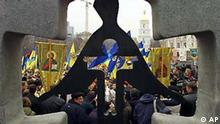 Some 2,000 people with Ukrainan flags and Orthodox gonfalons are seen through the monument to victims of the Great Famine in downtown Kiev, Ukraine, Saturday, Nov. 22, 2003. Ukraine marks on Saturday the 70th anniversary of the man-made Soviet-era famine that killed up to 10 milion Ukrainians in 1932-1933. (AP Photo/Andrei Lukatsky)