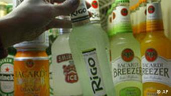 A hand holds a bottle in a fridge filled with alcoholic mix drinks