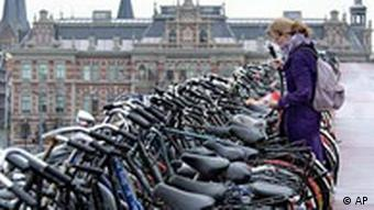A girl locks her bicycle at a three-storey bicycle parking area just outside Central Station in downtown Amsterdam