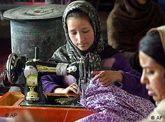 A girl in Afghanistan sews at a sewing machine