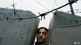 Mann linst durch die Mauer zwischen Israel und Palästina