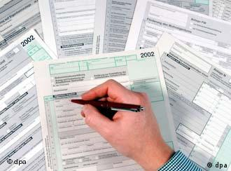 A hand holding a pen hovers over a pile of tax return forms