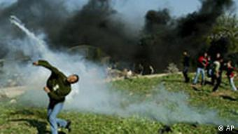 A Palestinian youth throws a tear gas canister back at Israeli troops, during a demonstration at the concrete separation barrier in the West Bank town of Qalqilya, Saturday, Dec. 27, 2003