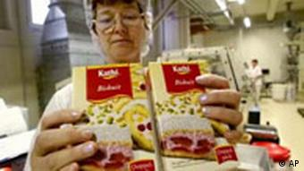 A woman holds out two cake mix boxes