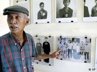 A survivor with pictures of other victims at the Khmer Rouge's notorious Tuol Sleng jail, now a museum