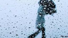 Durch die dicken Tropfen an einem Autofenster gesehen schuetzt sich eine Passantin mit ihrem Schirm gegen den heftigen Regen und Sturm am Montag, 12. Januar 2004, in der Naehe von Brotterode im Thueringer Wald. Im Laufe des Tages soll das Orkantief Gerda in Hoehenlagen ueber 600 Metern Windgeschwindigkeiten von bis 115 Kilomter pro Stunde erreichen. (AP Photo/Jens Meyer) --- A woman clutches her umbrella as she walks in heavy rain in the Thuringian Forest near Brotterode, eastern Germany, seen through the thick raindrops on a carwindow on Monday, Jan. 12, 2004. The current weather report predicts strong winds and heavy rain, or even snowfall on higher altitude regions in Germany on Monday. (AP Photo/Jens Meyer)