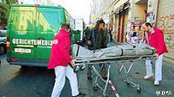 Forensic doctors in a city street transport a corpse on a hospital stretcher with wheels