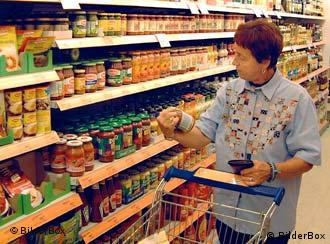 A woman looks at a jar in a supermarket