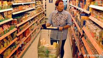 Seniorin in einem Supermarkt zwischen Regalen voller Lebensmittel