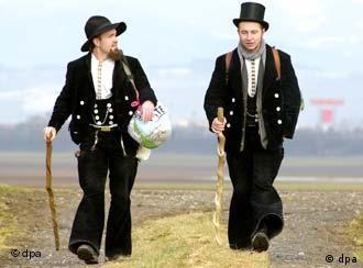 Zwei Gesellen, die in ihren traditionellen Anzügen durch ein Feld wandern und sich unterhalten.