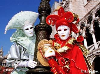 Zwei maskierte Personen stehen vor einem typisch venezianischen Gebäude