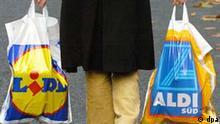 Eine Frau trägt am 17.11.2003 in der Innenstadt von Köln jeweils eine Plastiktüte der Lebensmittel-Discounter Lidl und Aldi. Deutschlands zweitgrößter Discounter Lidl tritt mehr und mehr aus dem Schatten des Branchenprimus Aldi. In den ersten drei Quartalen 2003 legte Lidl beim Umsatz rasant um 12,6 Prozent zu, Aldi (Nord und Süd) kam nur auf ein Plus von 5,6 Prozent. Besonders auffällig: Lidl knöpfte Aldi direkt Marktanteile ab. Im ersten Halbjahr verlor Aldi 78 Millionen Euro Umsatz an den schwäbischen Rivalen. Auch die Discounter Plus, Penny und Netto gaben zusammen Erlöse von 55 Millionen Euro an Lidl ab. Das berichtete die Gesellschaft für Konsumforschung (GfK) am 20. Oktober 2003 auf Anfrage.