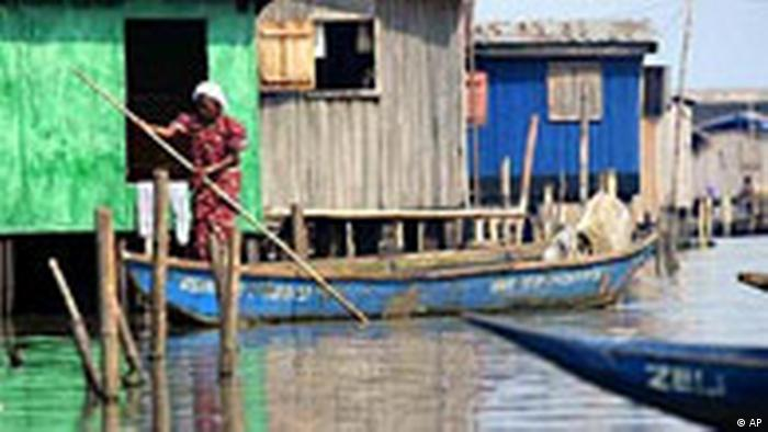A woman steers a canoe through wooden houses built on a lagoon in Lagos, Nigeria