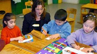 Kinder lesen mit ihrer Lehrerin (Foto: dpa)