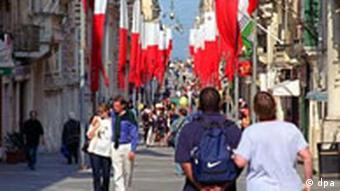 Many Maltese flags on a busy street