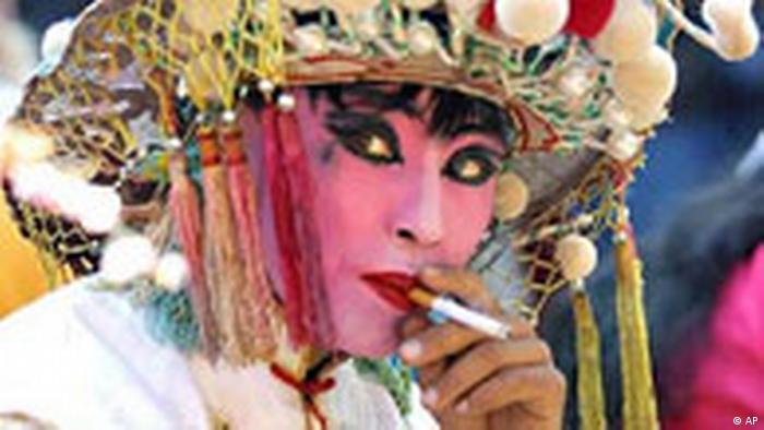 A performer takes a cigarette break between shows at a Lantern Festival celebration at a temple in Tianjin, east of Beijing, Tuesday, Feb. 26, 2002. The Lantern Festival, which falls on the 15th day of the Chinese Lunar New Year, marks the end of the traditional holiday period held to celebrate Spring Festival. China has the world's largest population of smokers, at more than 300 million. (AP Photo/str)