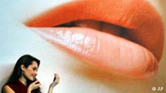 woman applies lipstick before a poster of lips