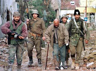 File photo of Yugoslav army soldiers and Serbian volunteers escorting a Croat civilian after entering Vukovar