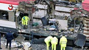 Spanish railway workers and police examine the debris of a bombed train at Madrid's Atocha railway station