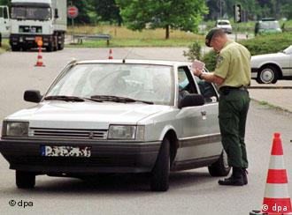 A traveler's passport is checked at the French-German border in 2000