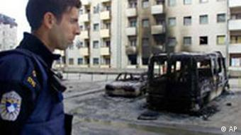 A Kosovo police officer stands guard near damaged cars and apartments in a mainly Serb neighborhood in the Kosovo capital Pristina after they were set on fire by ethnic Albanian protestors during overnight clashes between ethnic Albanians and Serbs. NATO peacekeepers and U.N. police are regrouping throughout Kosovo Thursday to put down rioting and violence that left eight dead and hundreds injured in one of the bloodiest days since the end of the Kosovo war in 1999. (AP Photo/Visar Kryeziu/18.03.2004)