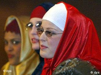 A Muslim woman adjusts the veil of a young girl during the 19th conference of the Union of Islamic Organizations of France (UOIF) at Le Bourget airport exhibition hall, north of Paris, on May 12, 2002