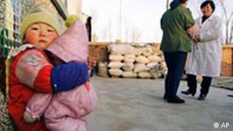 Li Xinyi,4, hugs a doll while her mother, Wang Ruihong talks with visiting family planning health care worker, Dr. Han Shuying, right, at Daliushu Village in northeast China's Hebei province, Jan. 29, 1997. China's central government is trying to make family planning easier to accept by providing better health care and more contraceptive choices. (AP Photo/Greg Baker)