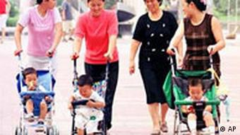 Chinese women push their babies in strollers at a park in Beijing Tuesday, Aug. 20, 2002. After more than two decades of the One Child policy, restrictions on the number of children a couple can have are being gradually relaxed. China's Anhui province has announced a new law allowing couples to have more than one child under certain conditions, while other provinces are considering similar laws. (AP Photo/str)