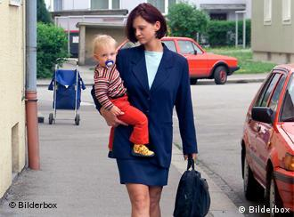 A woman in a business suit holding a young child