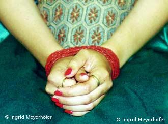 A woman sits with her hands bound in her lap