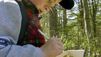A boy taking notes in the woods on a geocache