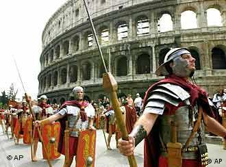 People dressed as ancient Roman centurions march in front of Rome's Colosseum