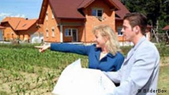 Architekt mit Bauherrin vor einem Rohbau