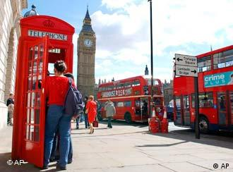 People in London's Parliment Square use a red phone box