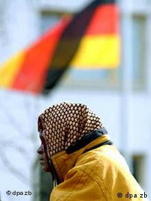 A refugee sits in front of a German flag