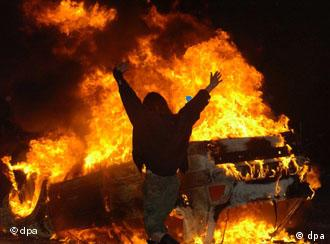 A demonstrator in Kreuzberg celebrating in front of a burning car
