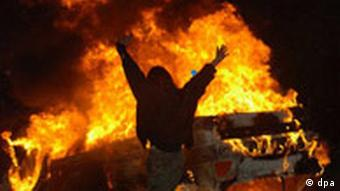 A man dances in front of a burning car