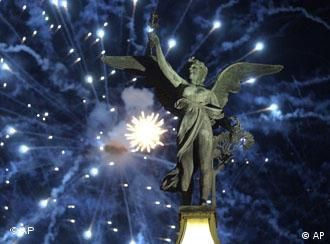 Fireworks explode over the statue of an angel on one of Prague's bridges