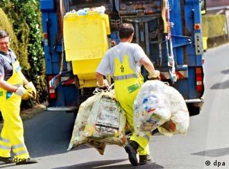 Garbage collectors bring bags of trash to a truck