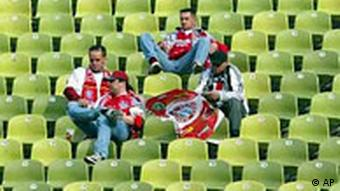 Three disappointed Bayern fans sitting among rows of empty seats at Munich's Olympia Stadium