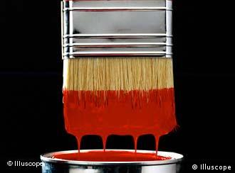 A paint brush dipped in a tin of red paint