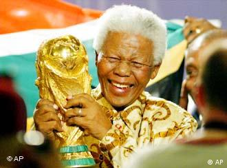 Former South African President Nelson Mandela lifts the World Cup trophy after the FIFA's executive committee announced that South Africa will host the 2010 FIFA World Cup