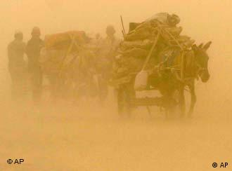 Uygur farmers rein donkey carriages against sandstorm in the suburbs of Yecheng, northwest China's Xinjiang Uygur Autonomous Region, Thursday, May 20, 2004. Strong sandstorm hit southern Xinjiang on Thursday. (AP Photo/Xinhua, Luo Xiaoguang)